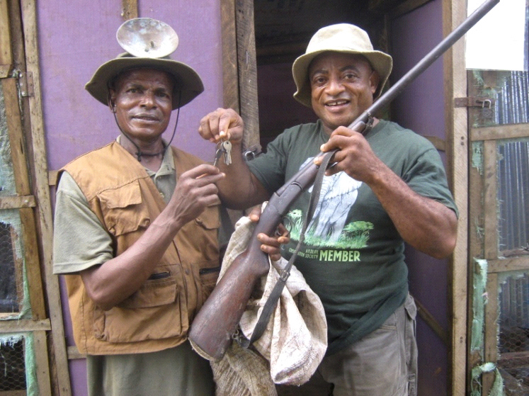 WCS education coordinator, Mark Otu (right), hands over the keys of a snail pen to one of the project beneficiaries, John Kidze, as he receives hunting gear from him (© WCS)